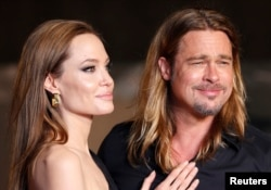 FILE - Hollywood actor Brad Pitt and actress Angelina Jolie make an appearance before fans at the Japan premiere of Pitt's movie 'World War Z' in Tokyo, July 2013.