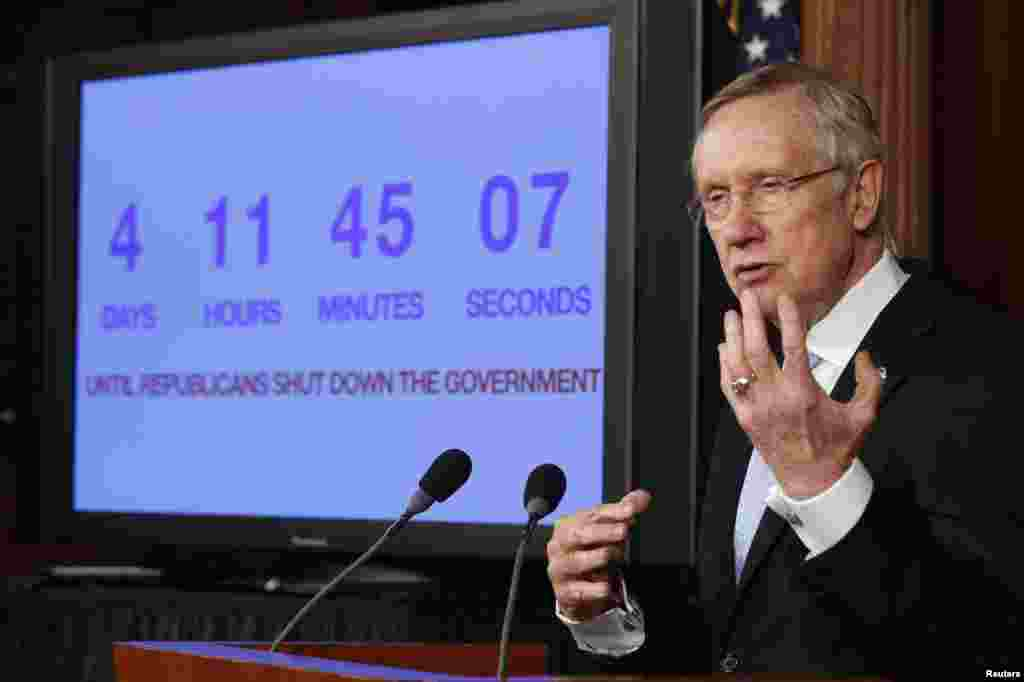 "U.S. Senate Majority Leader Harry Reid discusses the potential government shutdown, while standing in front of a countdown clock, on Capitol Hill in Washington, D.C. Reid, a Democrat, rejected plans by Republicans in the House of Representatives to advance a debt limit increase bill that contains measures such as delaying ""Obamacare."""