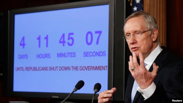 U.S. Senate Majority Leader Harry Reid discusses the potential U.S. government shutdown, while standing in front of a countdown clock, on Capitol Hill, Sept. 26, 2013.