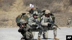 Tentara Angkatan Darat AS dan seorang tentara Korea Selatan memperagakan posisi mereka saat latihan militer bersama di Kompleks Lapangan Serbaguna di Pocheon, utara Seoul, Korea Selatan, Rabu (25/2).