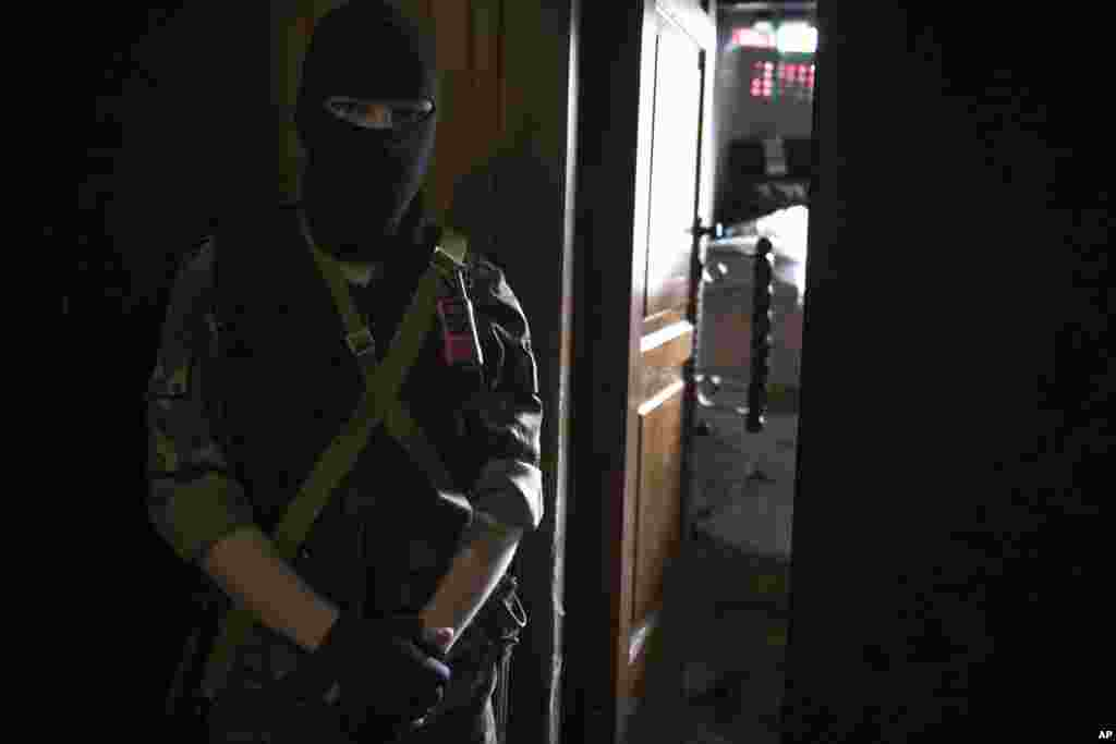 Seorang pemberontak pro-Rusia bertopeng menjaga pintu masuk kantor pemerintah daerah Ukraina di Luhansk (21/4). (AP/Alexander Zemlianichenko)