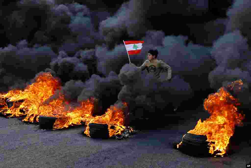 An anti-government demonstrator jumps over tires set on fire to block a main highway during a protest in the town of Jal el-Dib, north of Beirut, Lebanon.