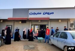 FILE - Libyans queue outside a supermarket in Tripoli on April 19, 2020.