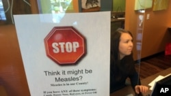 FILE - A sign warns of the dangers of measles in the reception area of a pediatrician's office in Scottsdale, Arizona, Feb. 7, 2015.