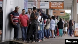 People line up before filling out applications while looking for job opportunities, in front of the building of an employment agency in Brasilia, Brazil, March 8, 2016.