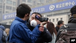 FILE - A plainclothes policeman grabs the hand of a foreign journalist as he prevents him from filming the supporters of rights lawyer Pu Zhiqiang's gathering near the Beijing Second Intermediate People's Court in Beijing, Dec. 14, 2015.