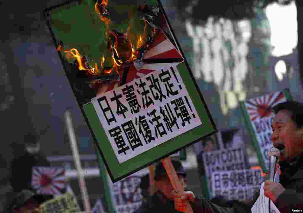 A protester from a right-wing, conservative and anti-Japanese civic group chants slogans denouncing Japanese PM Shinzo Abe's visit to the Yasukuni Shrine as he holds a placard that has been set alight, in front of the Japanese Embassy in Seoul.