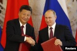 시진핑(왼쪽) 중국 국가주석과 블라디미르 푸틴 러시아 대통령이 4일 크렘린궁 회담후 합의문에 서명한 뒤 악수하고 있다.