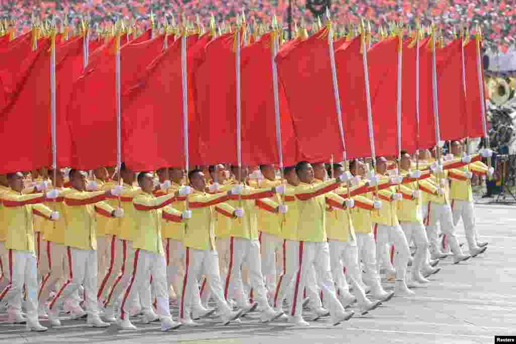 پریڈ کے شرکأ نے چین کا قومی پرچم تھاما ہوا تھا۔