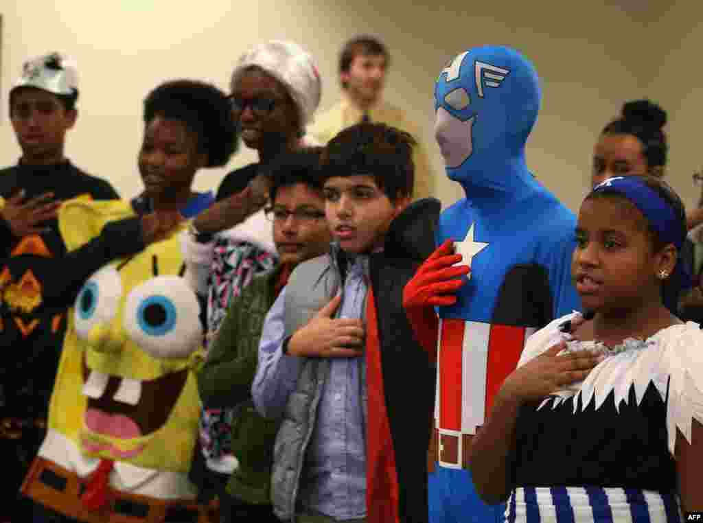 Children wearing Halloween costumes recite the Pledge of Allegiance after becoming US citizens during a naturalization ceremony at the United States Citizenship and Immigration Services in Baltimore, Maryland.