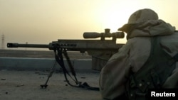 A sniper of the U.S. Marine Expeditionary Unit (MEU)takes aim in theport city of Umm-Qasr in southern Iraq on March 23, 2003 as his unitmet with pockets of resistance from the Republican Guard in aresidential area beside the port. Iraqi troops and paramil