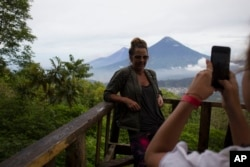 In this June 8, 2018 photo, a tourist poses for a photograph from a lookout point on ascent to the summit of the Pacaya volcano in San Francisco de Sales, Guatemala.