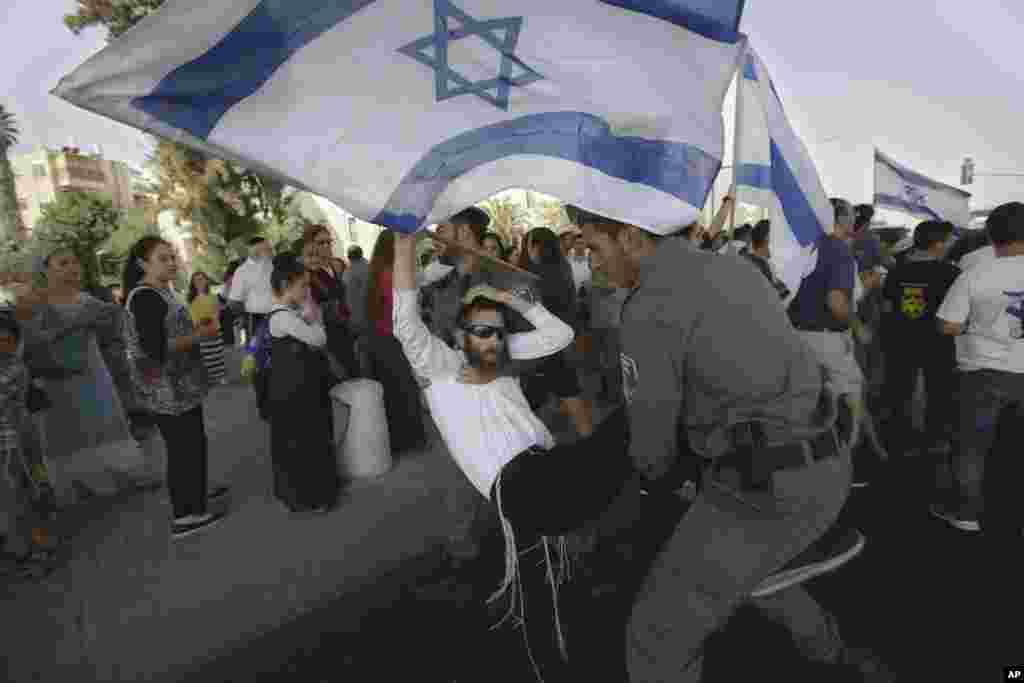 Israeli border police officers carry a right-wing protester after he attempted to block a road during a demonstration, a day after a drive-by shooting by suspected Palestinian gunmen killed a Jewish settler couple driving home with their children, in Jerusalem, Oct. 2, 2015.