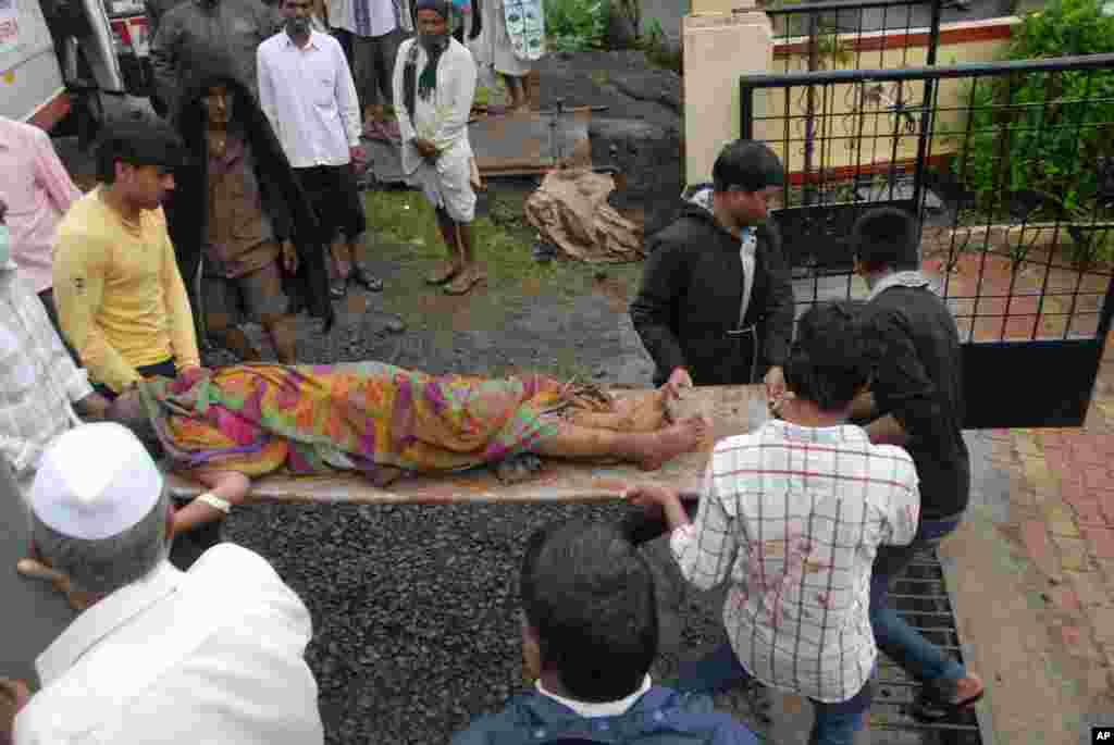 The body of a landslide victim is carried to a hospital in Ghodegaon village in the western Indian state of Maharashtra, Wednesday, July 30, 2014.