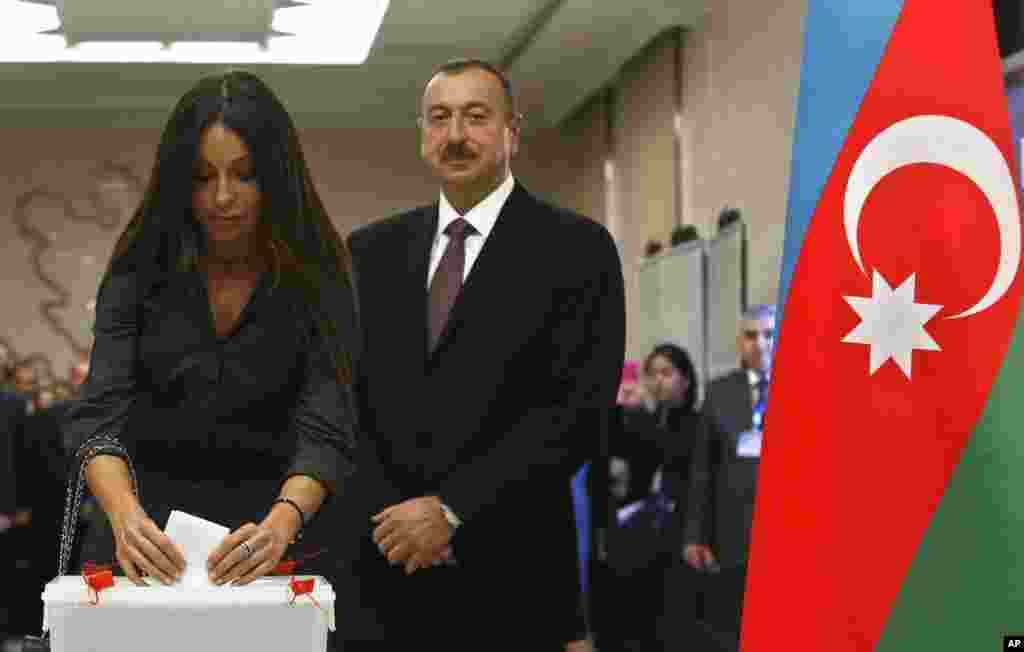 Azerbaijan President Ilham Aliyev looks on as his wife Mehriban casts her vote at a polling station in Baku, Oct. 9, 2013.