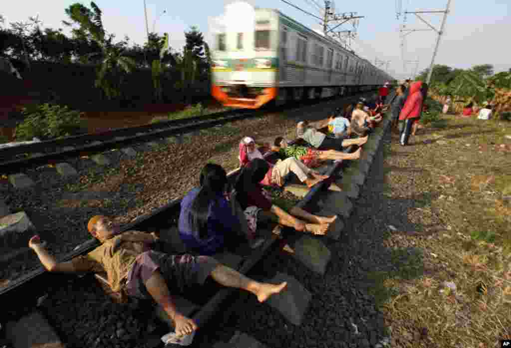 July 13: Residents lie on railway tracks in Rawa Buaya in Indonesia's West Java province. The residents believe that the electrical energy from the tracks will cure them of various illnesses. REUTERS/Enny Nuraheni