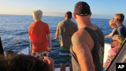 FILE - This Jan. 21, 2016, file photo shows tourists looking out on the horizon as their boat searches for dolphins in waters off Waianae, Hawaii.