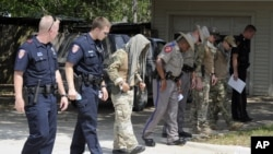 Law enforcement officials conduct a grid search of an area where police say a gunman was being served an eviction notice when he opened fire from inside a home near TexasA&M and killed a law enforcement officer Monday, Aug. 13, 2012, in College Station,