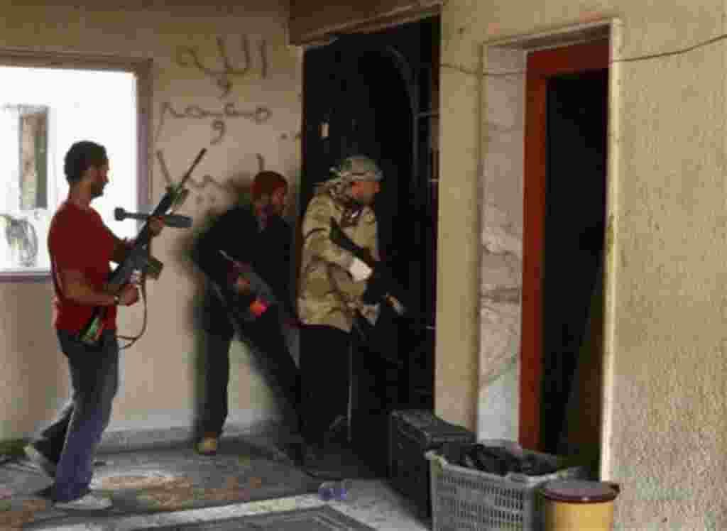 Combatientes rebeldes en búsqueda de un edificio de las fuerzas pro-Gadafi en la ciudad sitiada de Misrata, Libia, 23 de abril 2011.