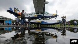 Un homme prend une photo d'un hydravion Cessna 208 Caravan 1 avant de quitter l'aérodrome de Juhu à Mumbai le 25 août 2014