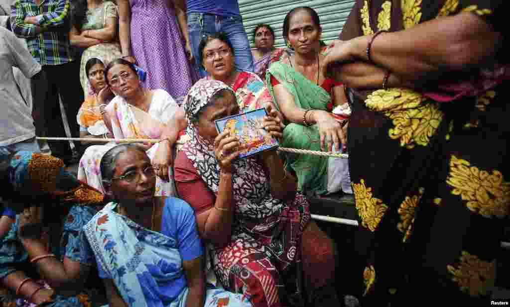Seorang perempuan berdoa bagi para kerabatnya yang terjebak di dalam reruntuhan gedung apartemen yang ambruk di Mumbai (27/9).