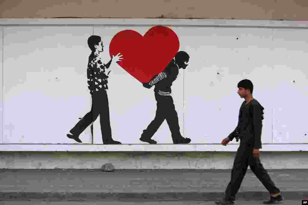 Một cậu bé người Afghanistan đi ở phía trước hình vẽ trên đường phố trên một bức tường rào của Cục An ninh ở Kabul.