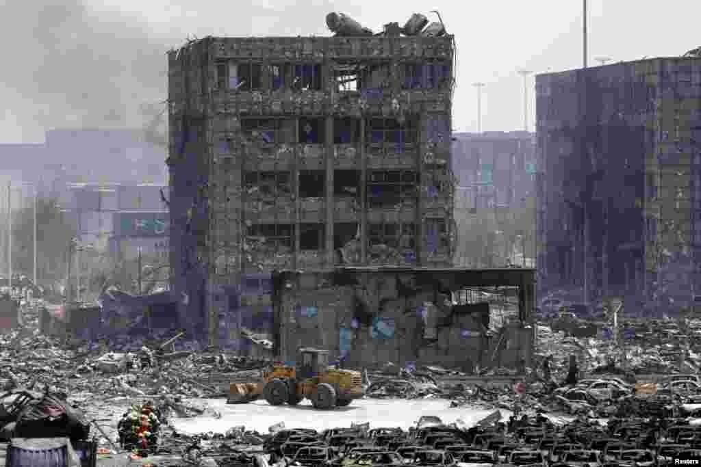 Bangunan dan mobil yang hancur terlihat di dekat lokasi ledakan di Binhai, Tianjin (13/8).