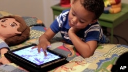 In this Oct. 21, 2011 file photo, Frankie Thevenot, 3, plays with an iPad in his bedroom at his home in Metairie, La. WHO announced that children under five years old should not spend more than one hour a day watching such devices.