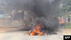 FILE - A barricade is set ablaze in the road during a protest in Mbabane, Eswatini, June 29, 2021. Residents have for months been holding rallies against Africa's last absolute monarchy