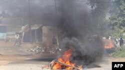 FILE - A barricade is set ablaze in the road during a protest in Mbabane, Eswatini, June 29, 2021.