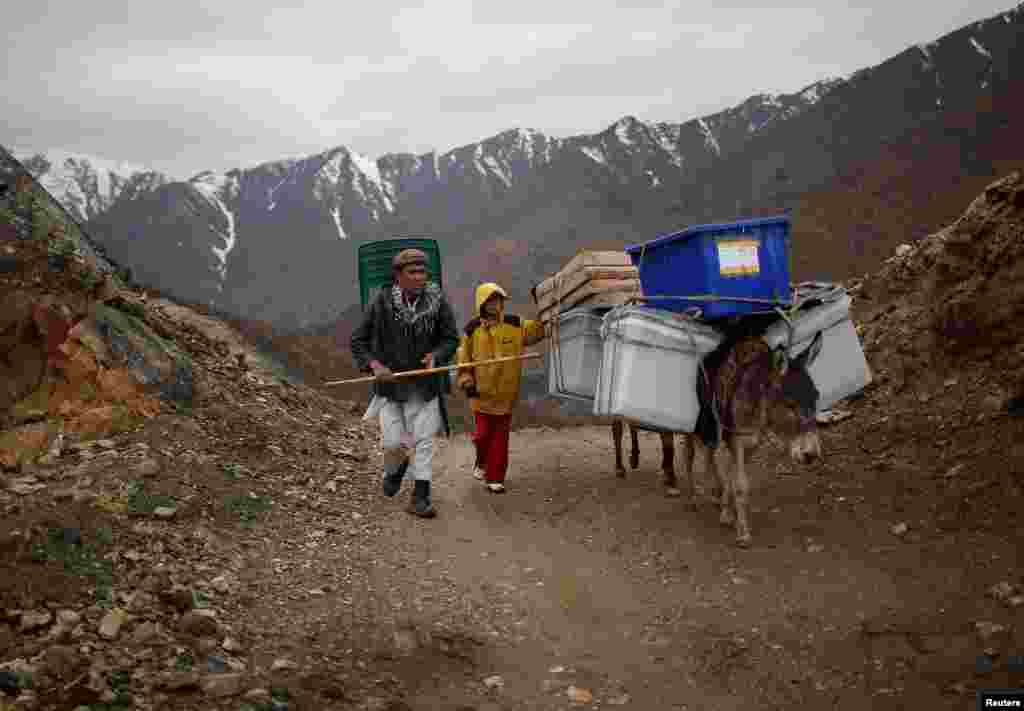 مردی همراه با پسرش الاغی را که بارش صندوق های رأی و برگه های انتخابات است به حوزه های رأی در مناطقی می برد که دسترسی جاده ای ندارد - شوتول، ولایت پنجشیر، ۵ آوریل ۲۰۱۴