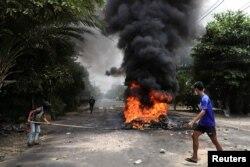 """Seorang pengunjuk rasa anti-kudeta berjalan melewati ban yang terbakar, setelah para aktivis melancarkan """"pemogokan sampah"""" terhadap aturan militer, di Yangon, Myanmar 30 Maret 2021. (REUTERS / Stringer)"""
