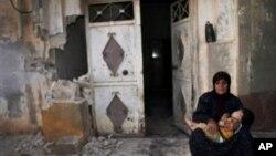 Женщина с ребенком на руках сидит у своего разрушенного обстрелом дома в сирийском городе Тремсе. 14 июля 2012 г.