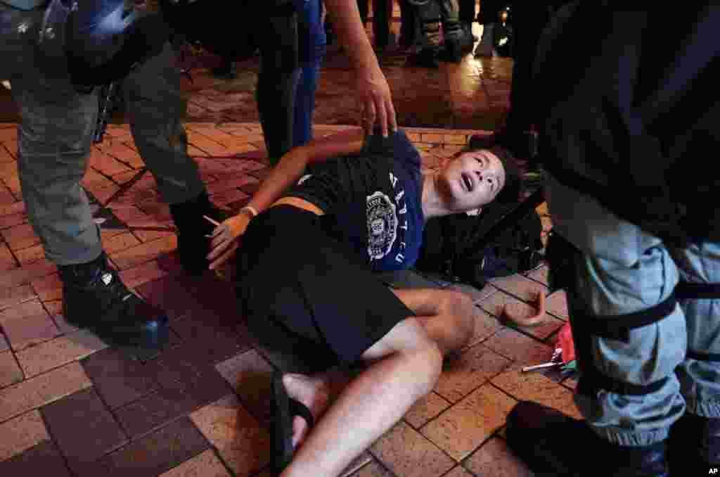 """La policía antidisturbios detiene a un manifestante en Hong Kong, el domingo 8 de septiembre de 2019. Miles de manifestantes en Hong Kong instan al presidente Donald Trump a """"liberar"""" el territorio chino semiautónomo durante una marcha pacífica al consulado de EE.UU., Pero la violencia estalló más tarde, en el distrito comercial y minorista, después de que los manifestantes destrozaron las estaciones de metro, incendiaron y bloquearon el tráfico. (Foto AP / Vincent Yu)"""