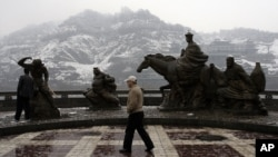 A visitor walks past the statues of the characters from the Chinese novel 'Journey to the West' Thursday March 15, 2007 in Lanzhou, China. Lanzhou was an important town along with the ancient Silk Road connecting China and Europe.