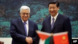 China's President Xi Jinping, right, shakes hands with his Palestinian counterpart Mahmoud Abbas during a signing ceremony at the Great Hall of the People in Beijing, China, May 6, 2013.