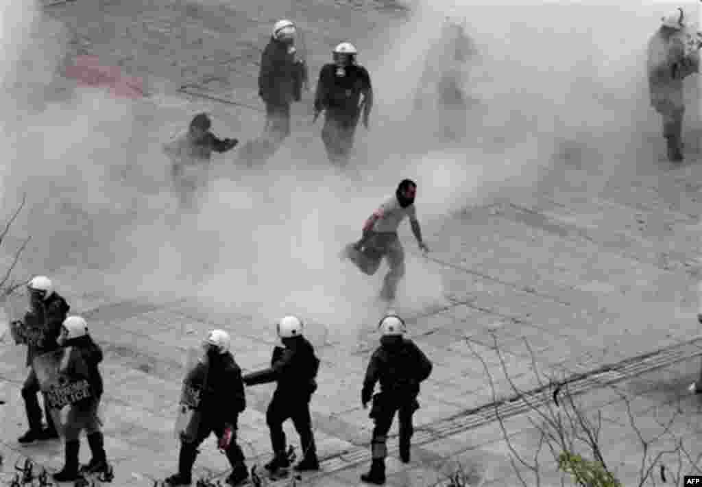 Protesters, center, run to avoid tear gas as riot police officers react during clashes in central Athens, Wednesday, Dec. 15, 2010. Hundreds of protesters clashed with riot police across central Athens Wednesday, smashing cars and hurling gasoline bombs d