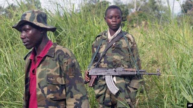 A child soldier helps man a checkpoint on the outskirts of Bunia, Congo, April 2011 (file photo).