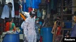 在孟买一处贫民窟,工作人员戴着智能温度扫描头盔在远距离检查人们的体温。 (2020年7月23日)
