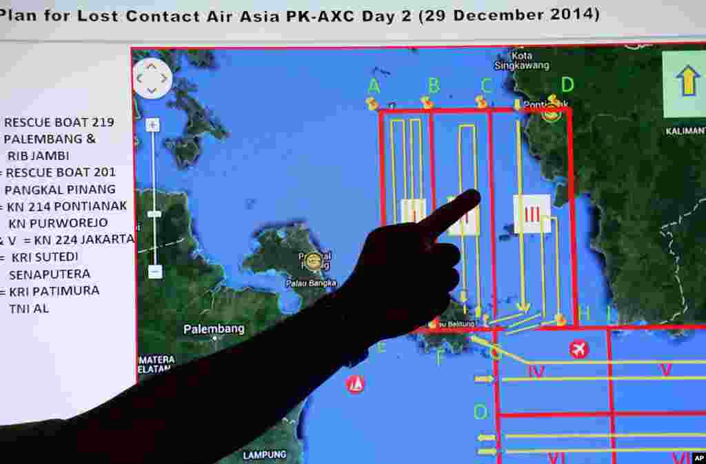 A member of the Indonesian National Search and Rescue Agency (BASARNAS) points to a map of a search area during a briefing prior to a search and rescue operation of the missing AirAsia flight 8501, at Pangkal Pinang command post in Sumatra Island, Indonesia, Dec. 29, 2014.