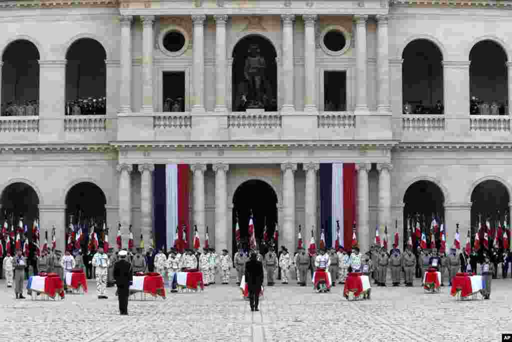French President Emmanuel Macron bows to coffins during a ceremony for the 13 French soldiers killed in Mali, at the Invalides monument in Paris.