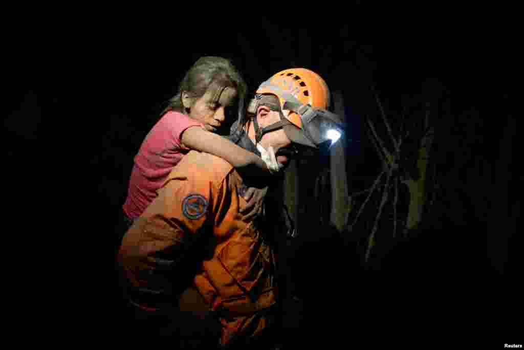A rescue worker carries a child covered with ash after Fuego volcano erupted violently in El Rodeo, Guatemala, June 3, 2018.