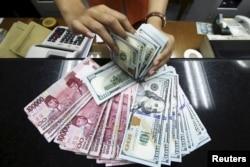 Seorang teller di tempat penukaran uang menunjukkan Rupiah dan dolar AS di Jakarta, 12 Agustus 2015. (Foto: Antara via Reuters)