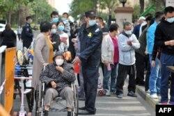 Warga antre di sepanjang jalan untuk tes Covid-19 di Qingdao, provinsi Shandong, China, 13 Oktober 2020.