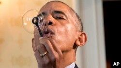 Predsednik Barak Obama duva balone koristeći štapić koji je uz pomoć 3D štampača napravio 9-godišnji Džejkob Leget