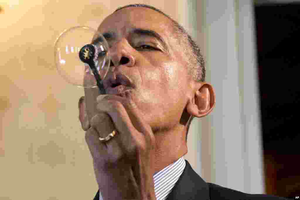 President Barack Obama blows a soap bubble using a 3-D printed bubble wand designed by Jacob Leggette, 9, of Baltimore, Maryland, while touring the 2016 White House Science Fair in Washington, April 13, 2016.