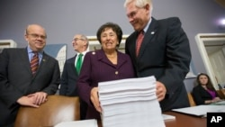 Rep. Pete Sessions, R-Texas, right, welcomes Rep. Nita Lowey, D-N.Y., and Rep. James P. McGovern, D-Mass., far left, as they gather at the Capitol around a printout of the $1.1 trillion spending bill to fund the government for fiscal 2016, Dec. 16, 2015.