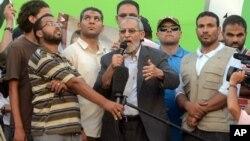 Pemimpin tertinggi Ikhwanul Muslimin, Mohammed Badie (tengah) berpidato di depan puluhan ribu pendukung Ikhwanul Muslimin, sementara helikopter militer terbang mengawasi aksi demo mereka di Kairo, 5 Juli 2013.
