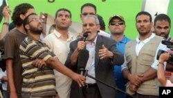 Лидер «Братьев-мусульман» Мохаммед Бади (в центре) выступает на митинге своих сторонников в Каире. Египет. 5 июля 2013 г.