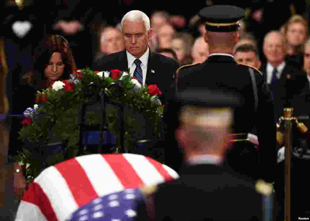 អនុប្រធានាធិបតីសហរដ្ឋអាមេរិកលោក Mike Pence (កណ្តាល) និងភរិយារបស់លោក គឺលោកស្រី Karen Pence (ឆ្វេង) គោរពវិញ្ញាណក្ខន្ធអតីតប្រធានាធិបតី George H.W. Bush នៅអាគារសភា Capitol ក្នុងអំឡុងពេលពិធីបុណ្យផ្លូវរដ្ឋក្នុងរដ្ឋធានីវ៉ាស៊ីនតោននៅថ្ងៃទី ០៣ ខែធ្នូ ឆ្នាំ២០១៨។